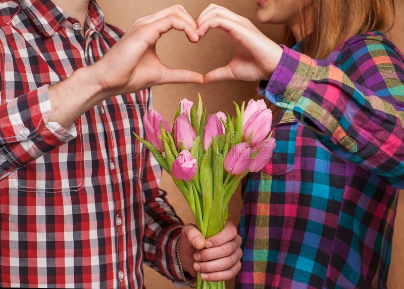 Het jonge paar in liefde maakt een hart en de handen houden tulpen. stock fotografie