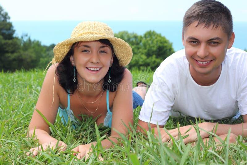 Het jonge paar ligt op gras stock foto's