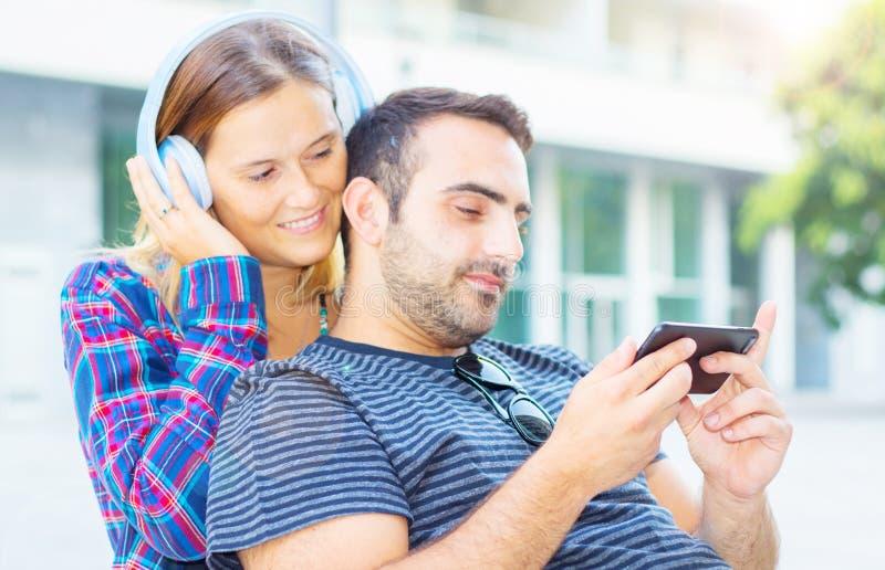 Het jonge paar luisteren en het letten op muziek op de telefoon royalty-vrije stock fotografie