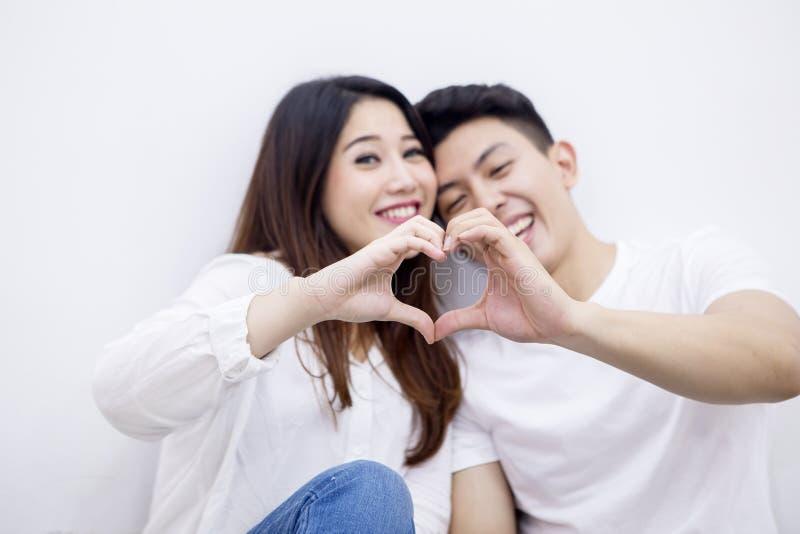 Het jonge paar maakt hartsymbool met hun handen stock foto's