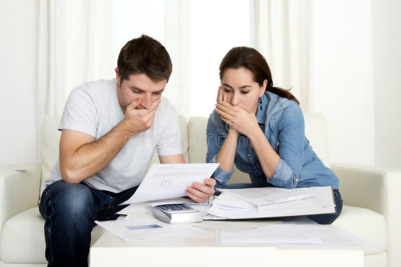 Het jonge paar maakte zich thuis in de bankbetalingen van de spanningsboekhouding ongerust royalty-vrije stock afbeelding