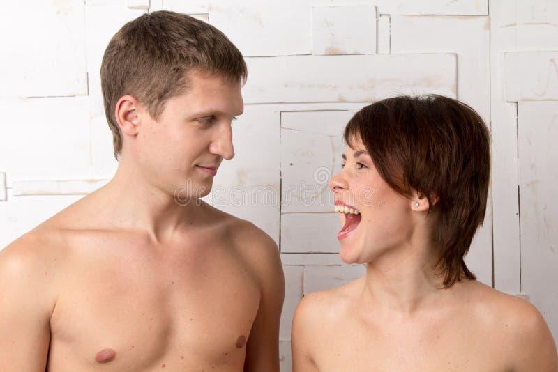 Het jonge paar met emoties van giecheelt dichtbij de witte muur royalty-vrije stock foto's