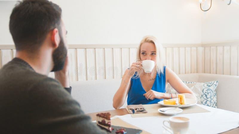 Het jonge paar neemt het menu om een orde bij de koffie te maken stock fotografie