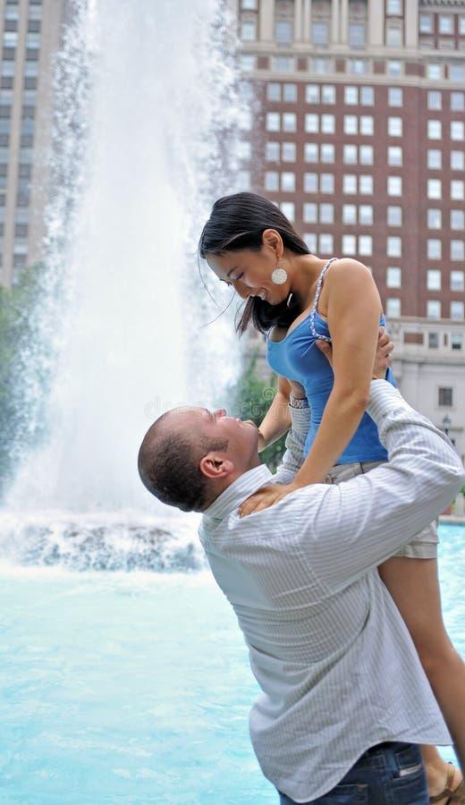 Het jonge paar omhelst voor fontein stock fotografie