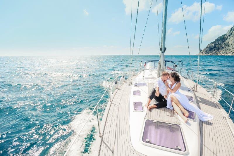 Het jonge Paar Ontspannen op een Jacht De gelukkige rijke man en een vrouw door priv? boot hebben overzeese reis stock afbeeldingen
