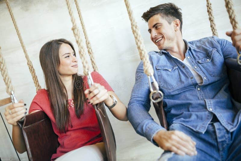 Het jonge paar ontspannen in schommeling stock afbeelding