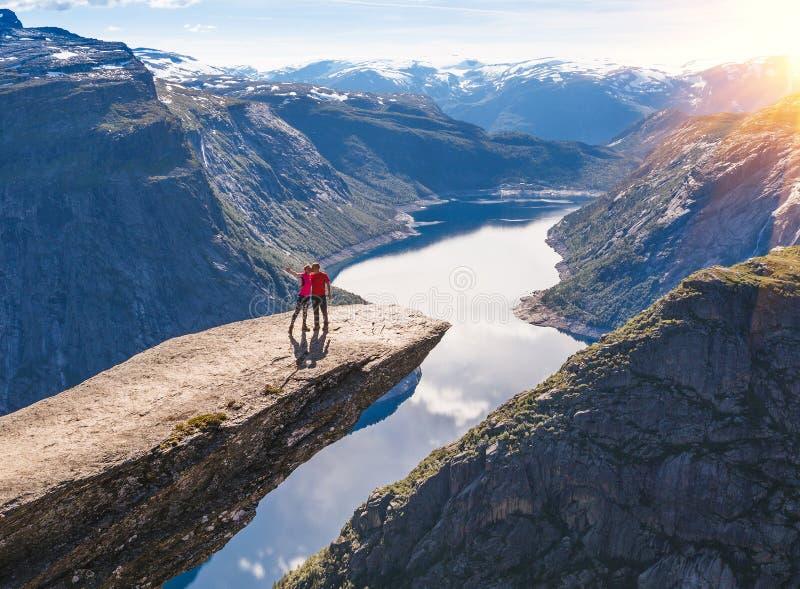 Het jonge paar ontspant op Trolltunga Het gelukkige meisje geniet van mooi meer en goed weer in Noorwegen stock fotografie