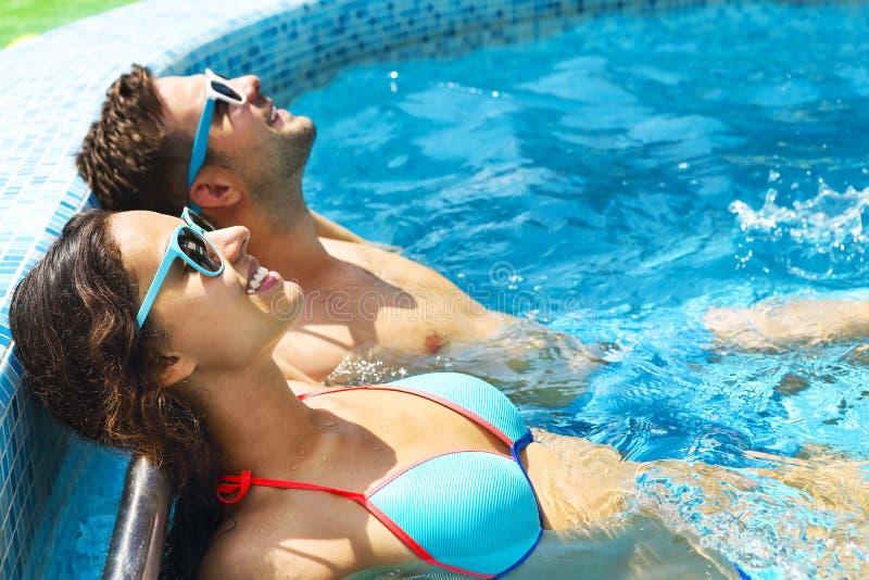 Het jonge paar ontspant in zwembad stock foto's