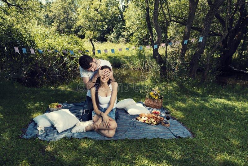 Het jonge paar op een picknickzitting op een deken de man behandelt haar ogen met handen stock foto