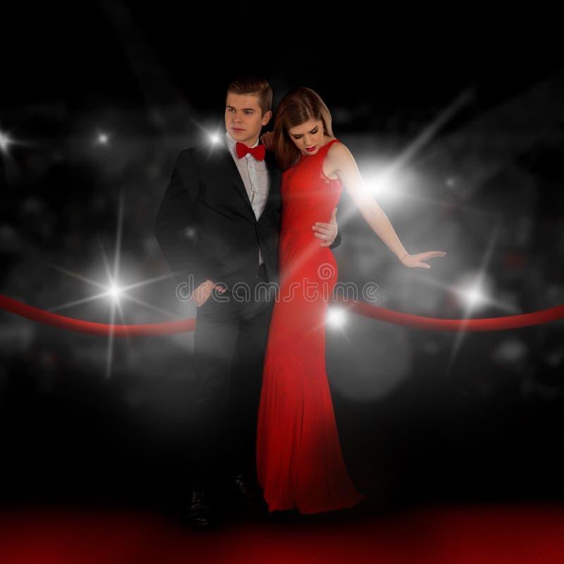 Het jonge paar op rood tapijt stelt in paparazziflitsen stock fotografie