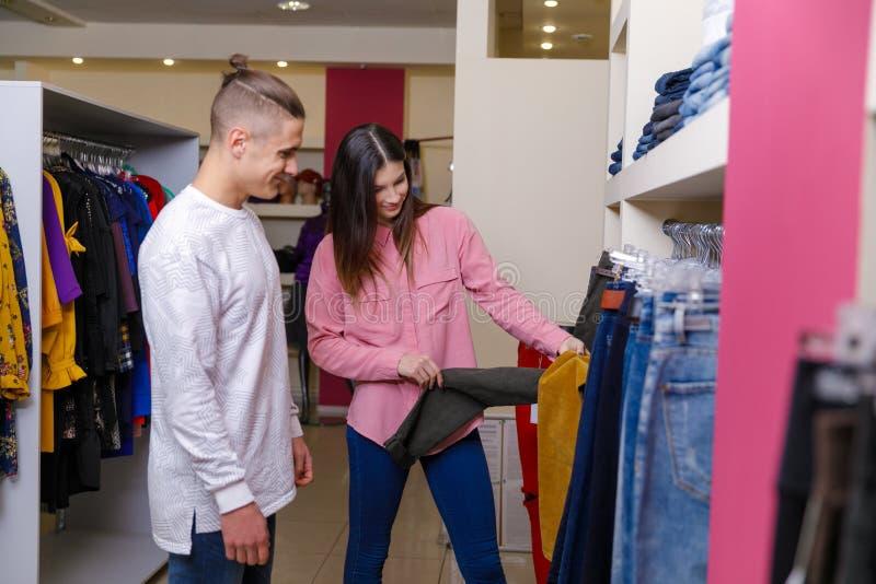 Het jonge paar overweegt kleren in winkel Jong aardig paar in winkel met aankopen stock fotografie