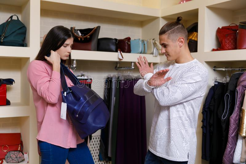 Het jonge paar overweegt kleren in winkel Jong aardig paar in winkel met aankopen stock afbeelding