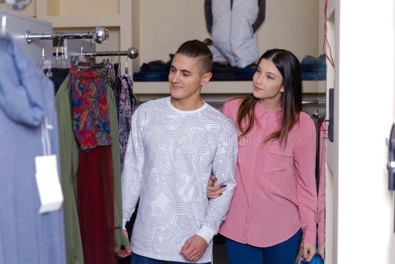 Het jonge paar overweegt kleren in winkel Jong aardig paar in winkel met aankopen royalty-vrije stock fotografie