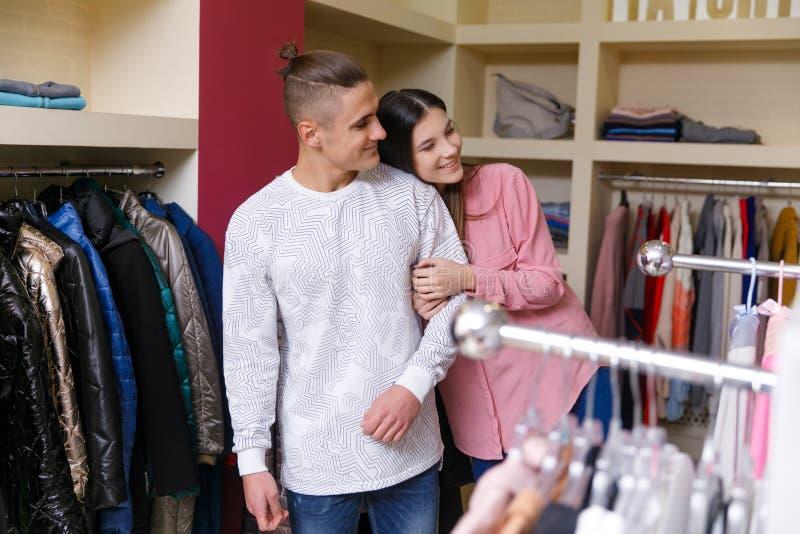 Het jonge paar overweegt kleren in winkel Jong aardig paar in winkel met aankopen stock afbeeldingen