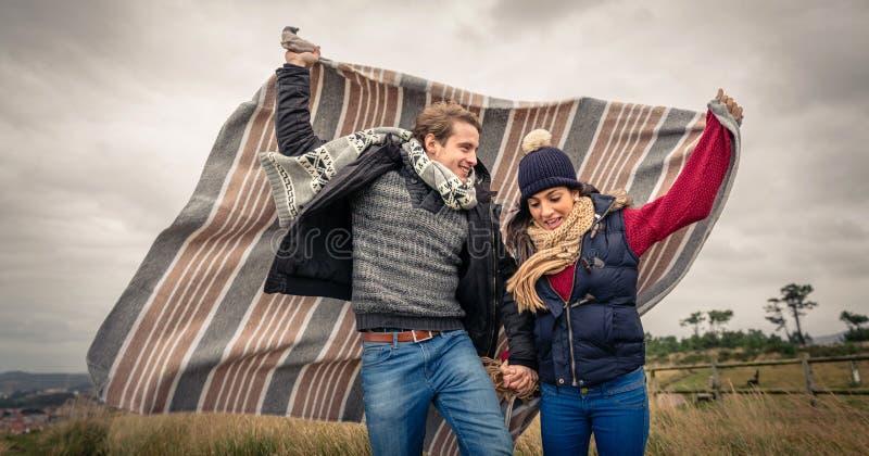 Het jonge paar spelen in openlucht met deken in een winderige dag stock afbeeldingen