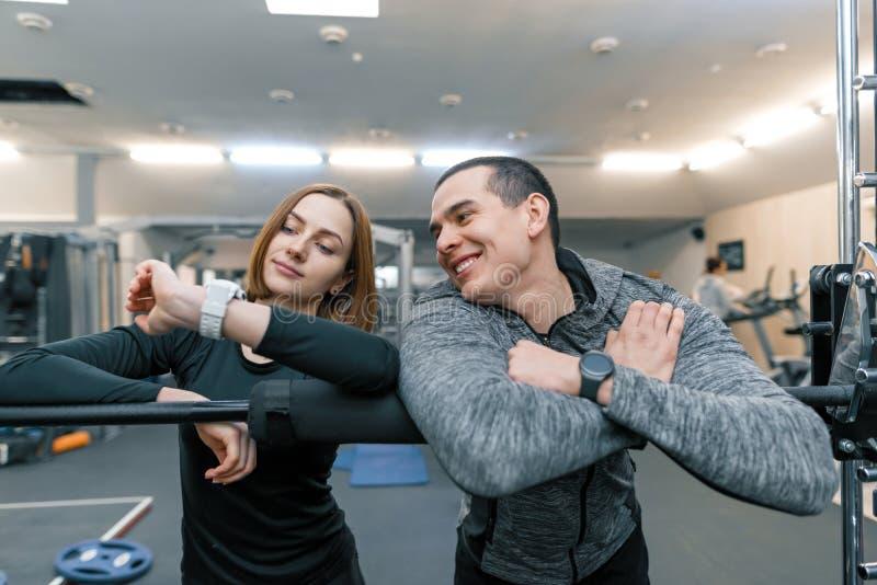 Het jonge paar spreken die de klok, gezonde levensstijl, gymnastiekachtergrond bekijken royalty-vrije stock afbeeldingen