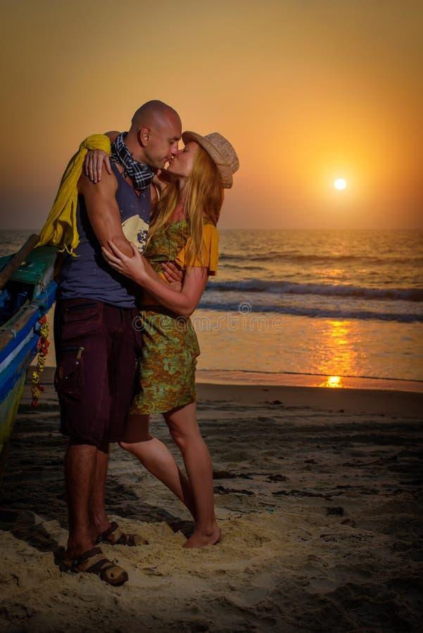 Het jonge paar stellen tegen overzees bij zonsondergang Kerel en meisjes het voor de gek houden en grimas dichtbij de oude houten royalty-vrije stock foto