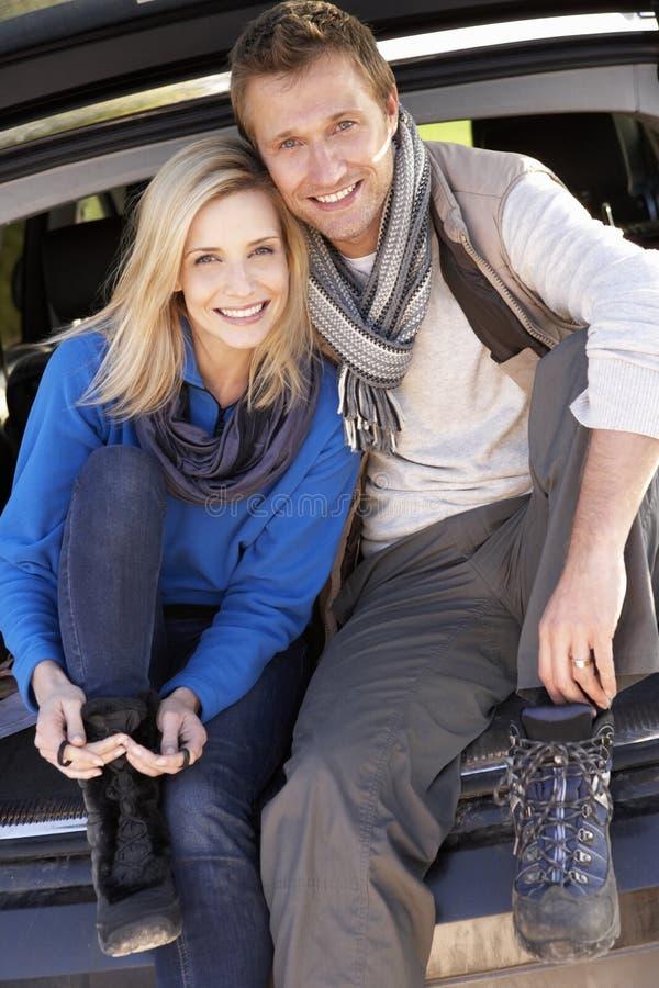 Het jonge paar stelt samen bij achtergedeelte van auto stock foto