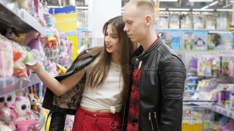 Het jonge paar in supermarkt kiest zacht stuk speelgoed voor gift stock afbeelding