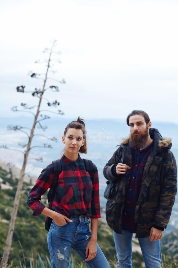 Het jonge paar van toeristen beklom tot de bovenkant van de heuvel en geniet van een mooie mening stock foto