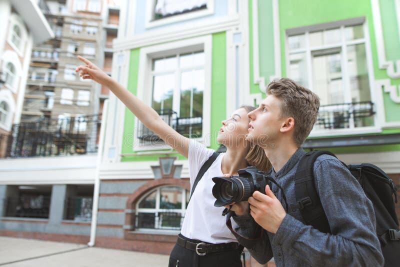 Het jonge paar van toeristen die rond de oude stad lopen, een aantrekkelijk meisje toont een hand stock afbeelding