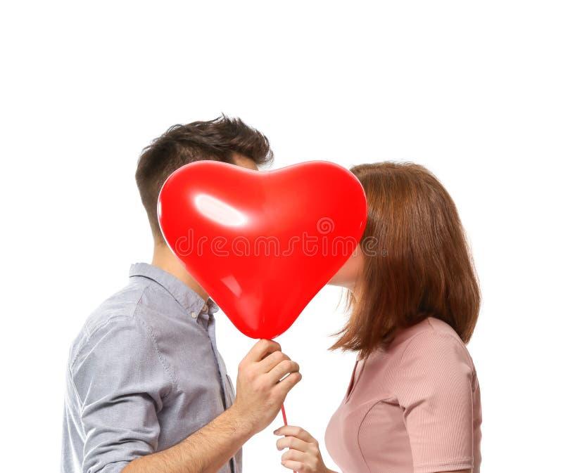 Het jonge paar verbergen achter hart-vormige ballon op witte achtergrond Viering van de Dag van Heilige Valentine royalty-vrije stock foto