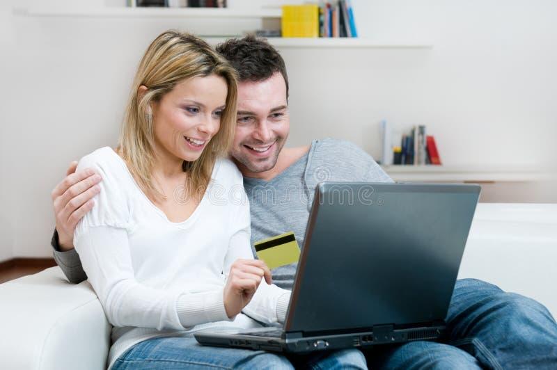 Het jonge paarInternet winkelen stock foto
