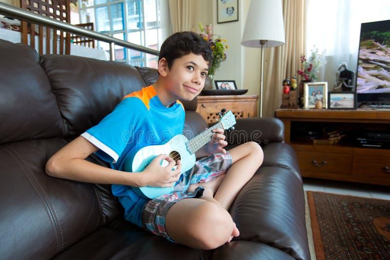 Het jonge pan Aziatische jongen praktizeren op zijn blauwe ukelele in een huismilieu royalty-vrije stock fotografie