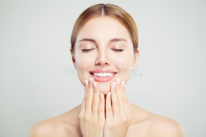 Het jonge perfecte vrouwengezicht met roze glanzende lippen en manicured handen met Franse manicurespijkers royalty-vrije stock fotografie