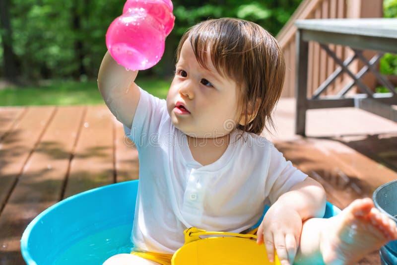 Het jonge peuterjongen spelen met water stock fotografie