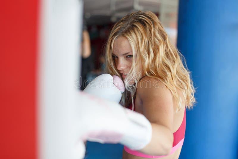 Het jonge ponsen van de blondevrouw in zware zak in gymnastiek stock fotografie