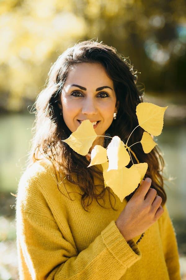 Het jonge portret van de vrouwenherfst met gele bladeren stock foto's