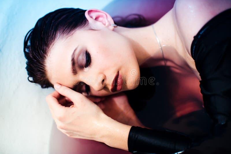 Het jonge prettige kijken vrouwelijk model geniet van heet bad, toont haar naakte schouders Schoonheid en zorgconcept royalty-vrije stock foto's
