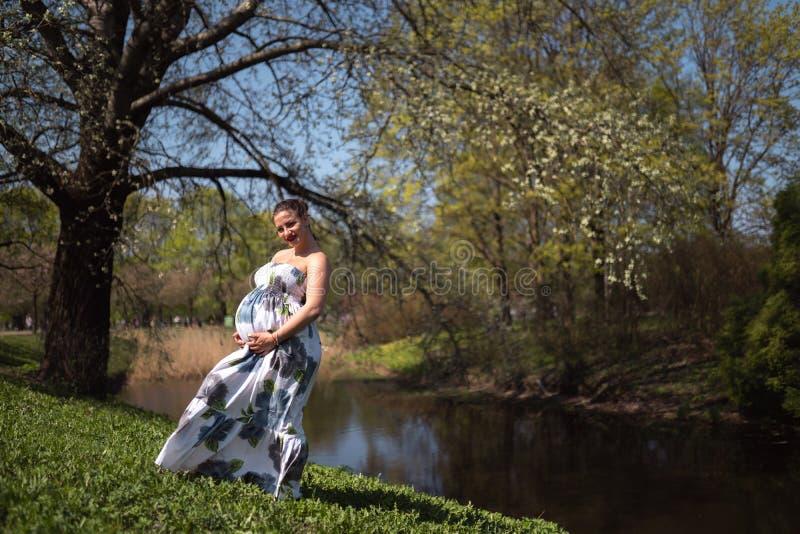 Het jonge reizigers zwangere vrouw lopen, lopend, zich omdraait en geniet van haar vrije tijdsvrije tijd in een park met stock afbeelding