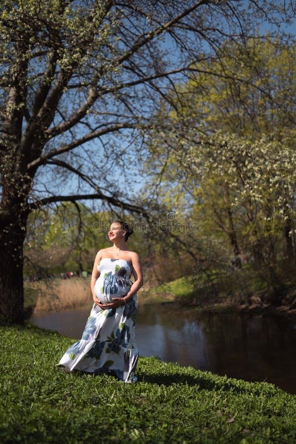 Het jonge reizigers zwangere vrouw lopen, lopend, zich omdraait en geniet van haar vrije tijdsvrije tijd in een park met royalty-vrije stock afbeelding
