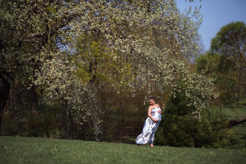 Het jonge reizigers zwangere vrouw lopen, lopend, zich omdraait en geniet van haar vrije tijdsvrije tijd in een park met royalty-vrije stock afbeeldingen