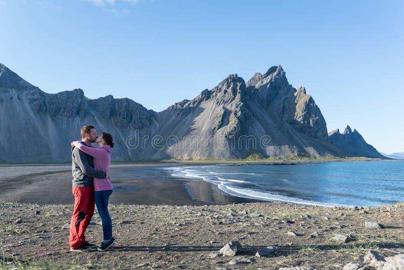 Het jonge romantische paar kussen bij een toneelstrand in Stokksnes ijsland royalty-vrije stock afbeeldingen