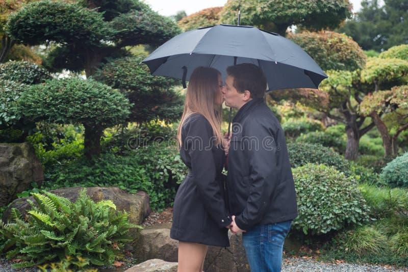 Het jonge romantische paar kussen onder paraplu buiten stock fotografie