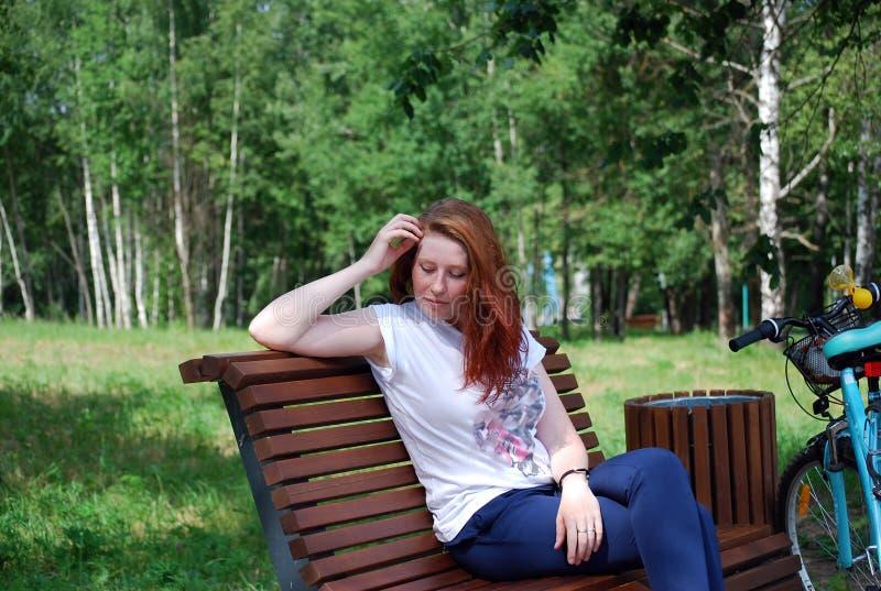 Het jonge roodharige die meisje met fiets is gegaan zitten om een rust op een winkel te hebben en omhoog te doen liet neer haar royalty-vrije stock foto