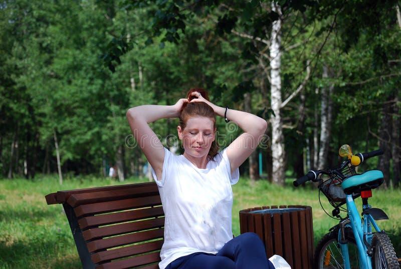 Het jonge roodharige die meisje met fiets is gegaan zitten om een rust op een winkel te hebben en omhoog te doen liet neer haar royalty-vrije stock foto's