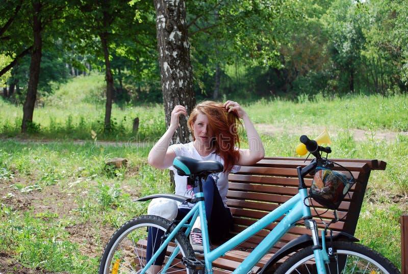 Het jonge roodharige die meisje met fiets is gegaan zitten om een rust op een winkel te hebben en omhoog te doen liet neer haar stock fotografie