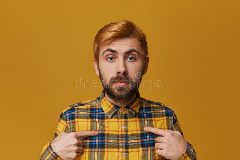 Het jonge roodharige gebaarde mannetje draagt geruit geel die overhemd en verbaasd punt met een vinger op zijn zelf wordt verward royalty-vrije stock afbeelding