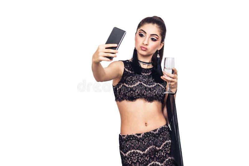 Het jonge schitterende meisje houdt een glas van champagne en het nemen selfie stock afbeelding