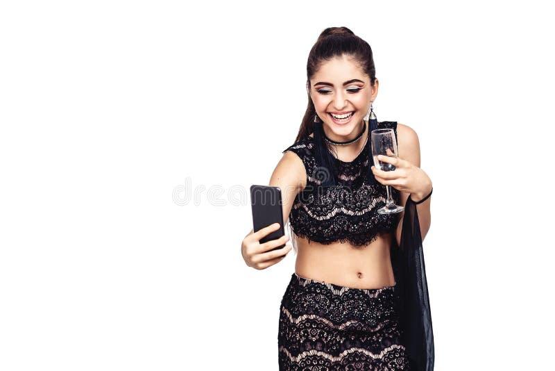 Het jonge schitterende meisje houdt een glas van champagne en het nemen selfie royalty-vrije stock foto