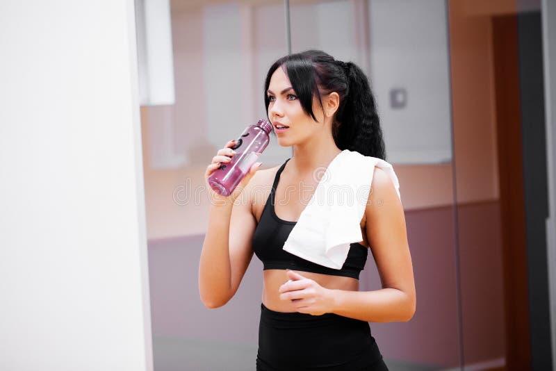 Het jonge schone water van de vrouwendrank in geschiktheidsgymnastiek stock afbeeldingen