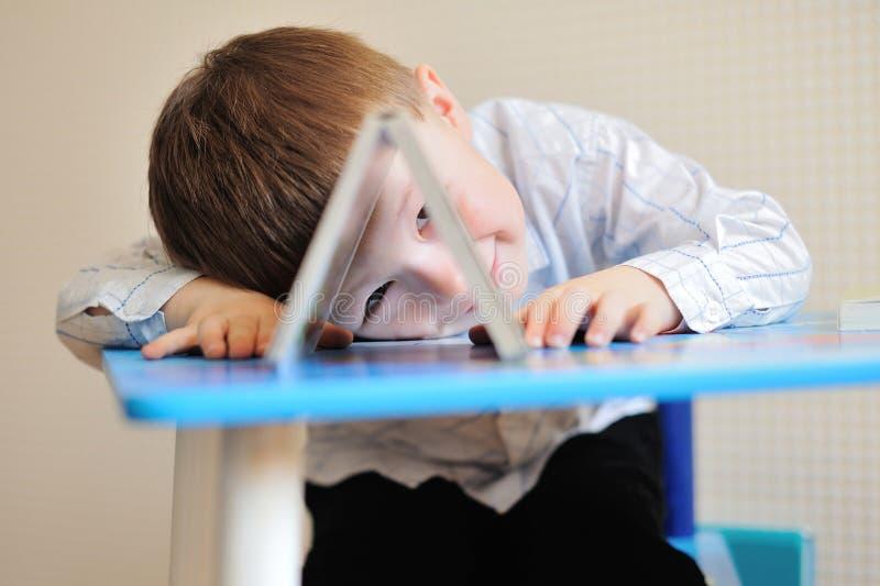 Het jonge schooljongen spelen met boeken en het glimlachen aangezien hij bij zijn bureau in klaslokaal zit royalty-vrije stock afbeeldingen