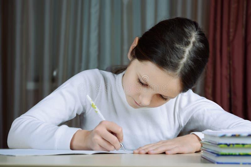 het jonge schooljongenmeisje doet zijn thuiswerk royalty-vrije stock foto