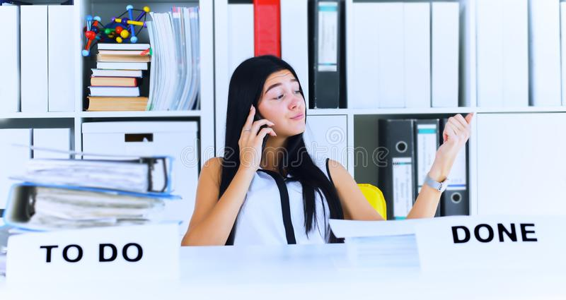 Het jonge secretaresse spreken op de telefoon vergeet over heel wat administratie, die niet wordt gedaan Inefficiënt gebruik van  stock fotografie