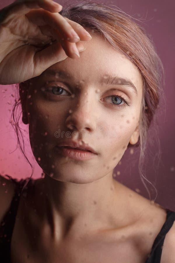 Het jonge sensuele meisje zet haar gezicht op haar hand en leunt op glas waarop de vage dalingen van water neer stromen Droevig c royalty-vrije stock foto's