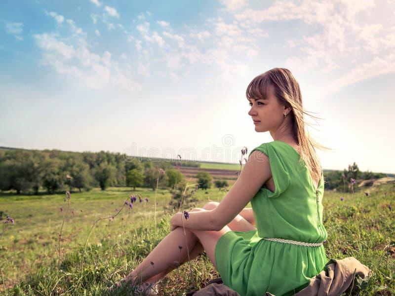 Het jonge sensuele meisje zit in openlucht in een gras royalty-vrije stock fotografie